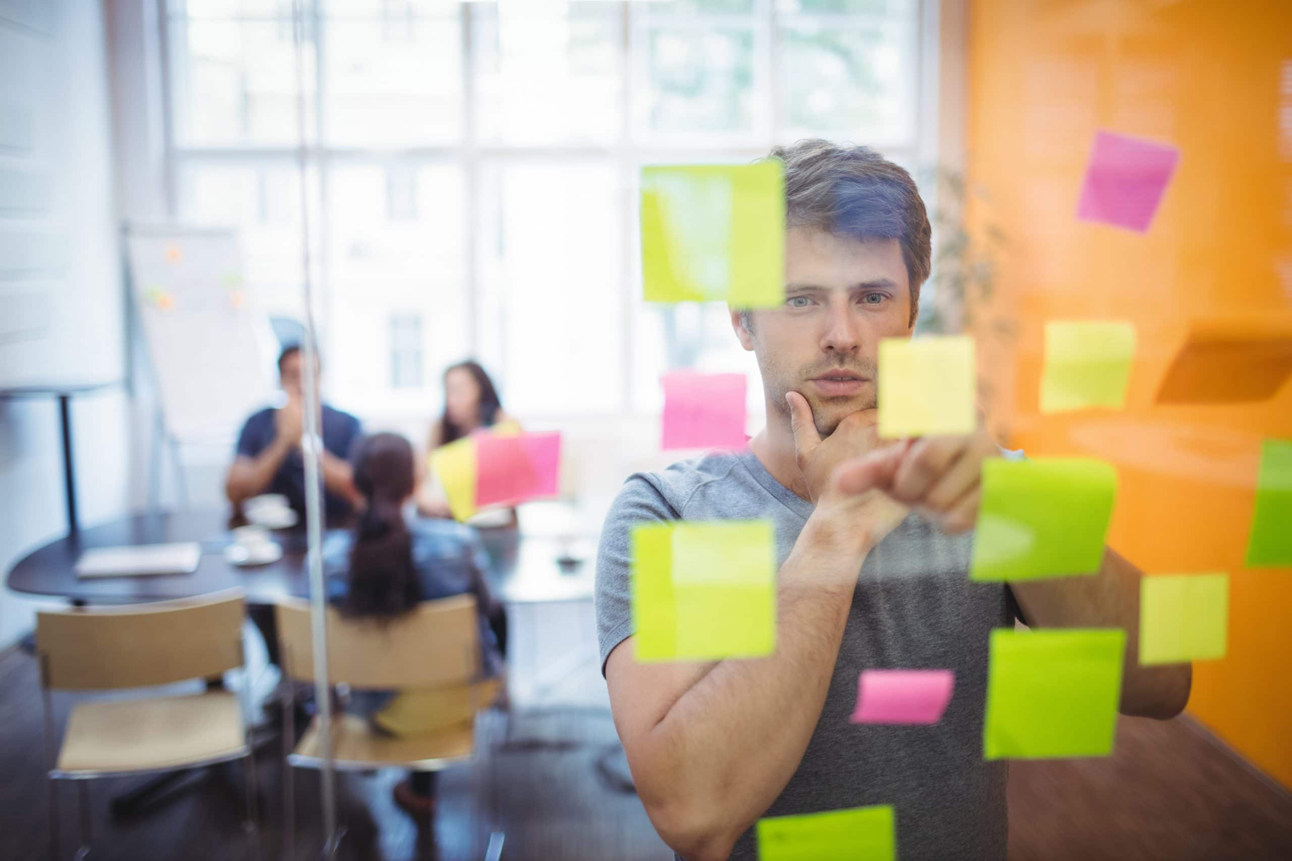 Close-up of male executive reading sticky notes in office